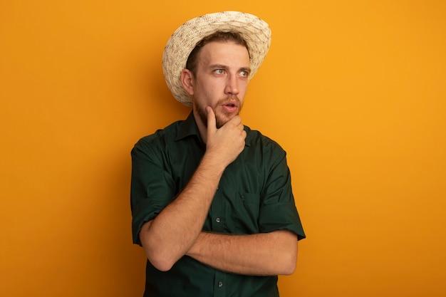 Überraschtes hübsches blondes mann mit strandhut legt hand auf kinn und schaut auf seite lokalisiert auf orange wand