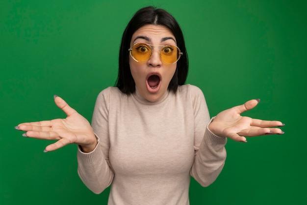 Überraschtes hübsches brünettes kaukasisches mädchen in der sonnenbrille hält hände offen auf grün