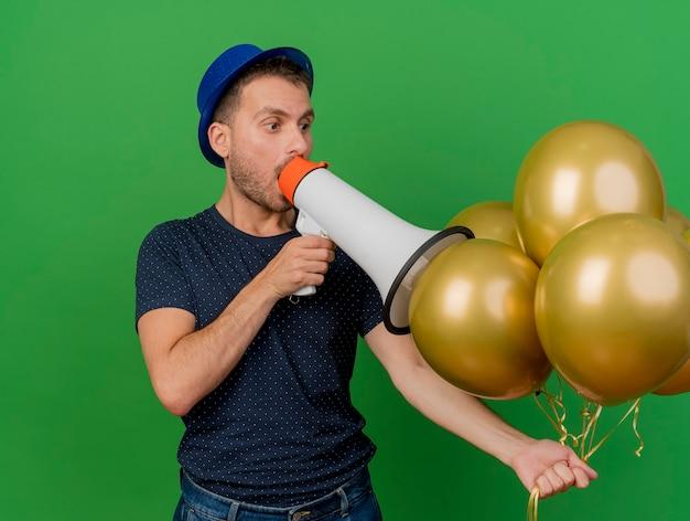 Überraschtes hübsches kaukasisches mann, das blauen parteihut trägt, hält heliumballons und spricht in lautsprecher, der auf grünem hintergrund mit kopienraum isoliert wird