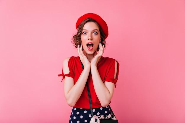 Überraschtes hübsches mädchen in der französischen baskenmütze, die mit offenem mund aufwirft. kaukasische dame in der eleganten roten bluse stehend.