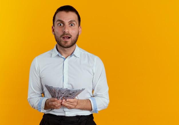 Überraschtes hübsches mann hält geld, das auf orange wand lokalisiert aussieht