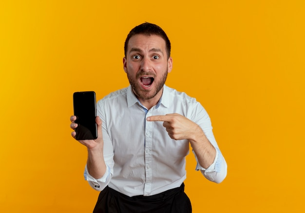 Überraschtes hübsches mann hält und zeigt auf telefon, das auf orange wand lokalisiert schaut