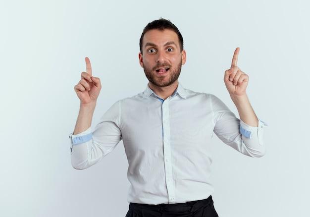 Überraschtes hübsches mann zeigt mit zwei händen, die isoliert auf weißer wand schauen
