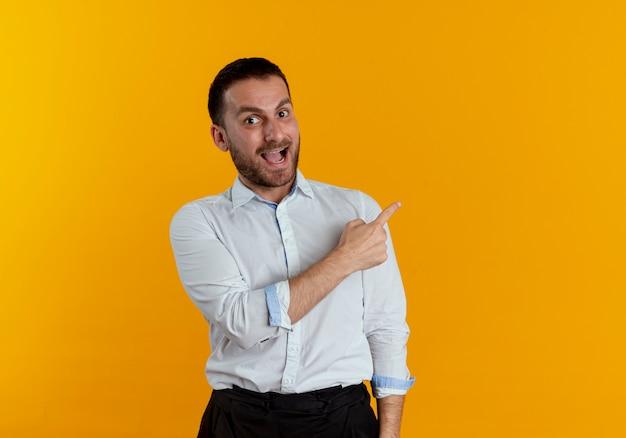 Überraschtes hübsches mann zeigt zur seite, die lokal auf orange wand schaut