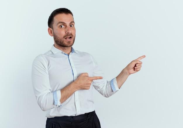 Überraschtes hübsches mann zeigt zur seite mit zwei händen, die isoliert auf weißer wand suchen