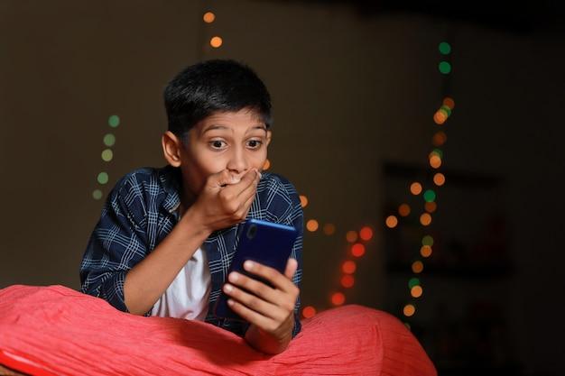 Überraschtes indisches kleines kind nach dem sehen im smartphone