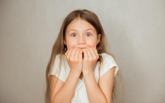 Überraschtes jugendlich mädchen steckt ihre finger in den mund