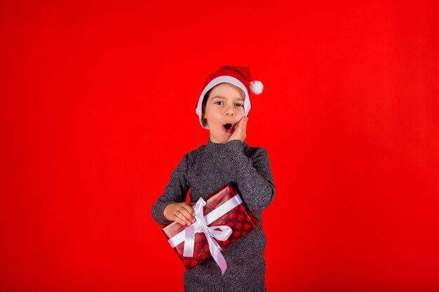 Überraschtes jungenkleinkind in einem pullover und einem roten hut des neuen jahres mit einem geschenk auf rot