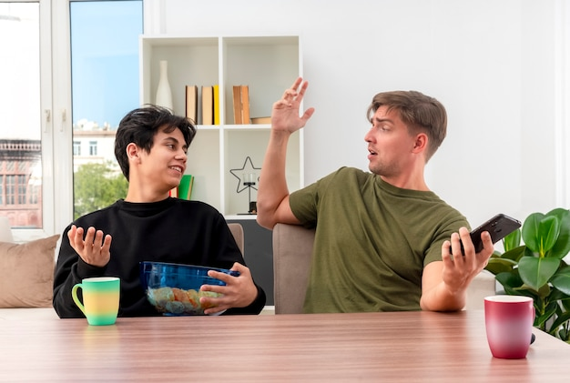 Überraschtes junges blondes hübsches mann hält telefon und hebt hand, die am tisch sitzt und einander mit erfreutem jungem brünettem hübschem kerl betrachtet, der schüssel chips innerhalb des wohnzimmers hält