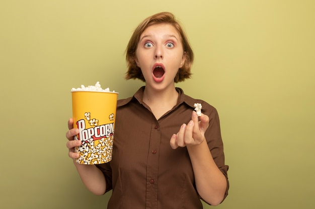 Überraschtes junges blondes mädchen, das eimer mit popcorn und popcornstück isoliert auf olivgrüner wand mit kopienraum hält