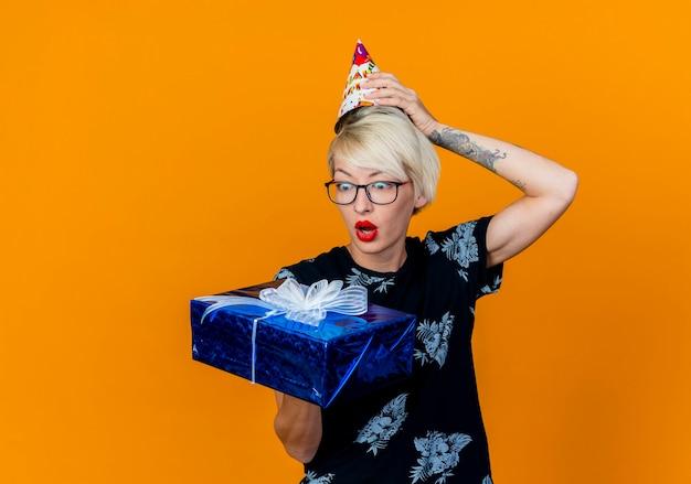 Überraschtes junges blondes partygirl, das brille und geburtstagskappe hält und geschenkbox hält, die hand auf kappe lokalisiert auf orange hintergrund mit kopienraum hält