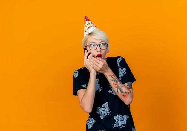 Überraschtes junges blondes partygirl, das brille und geburtstagskappe trägt, die am telefon sprechen hand in der nähe des mundes halten und seite betrachten, die auf orange hintergrund mit kopienraum lokalisiert wird