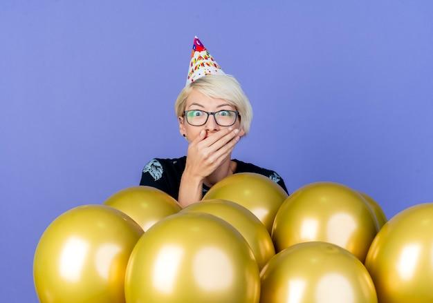Überraschtes junges blondes partygirl, das brille und geburtstagskappe trägt, die hinter luftballons steht, die hand auf mund lokalisiert auf lila hintergrund halten