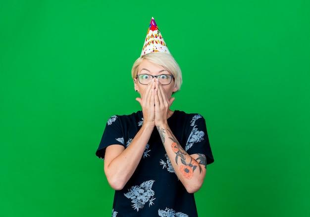 Überraschtes junges blondes partygirl, das brille und geburtstagskappe trägt, die kamera betrachtet, die hände auf mund lokalisiert auf grünem hintergrund mit kopienraum hält