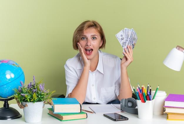 Überraschtes junges blondes studentenmädchen, das am schreibtisch mit schulwerkzeugen sitzt und die hand auf dem gesicht hält, das geld hält
