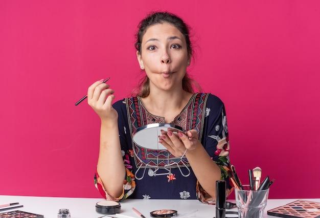 Überraschtes junges brünettes mädchen, das am tisch mit make-up-tools sitzt und fischgesicht macht und spiegel isoliert auf rosa wand mit kopienraum hält