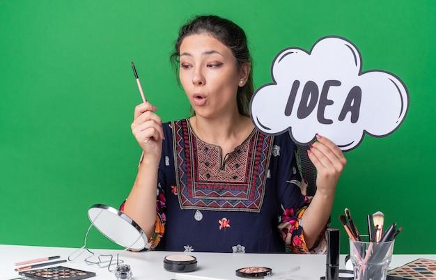 Überraschtes junges brünettes mädchen, das am tisch mit make-up-tools sitzt und ideenblase hält und make-up-pinsel einzeln auf grüner wand mit kopienraum betrachtet