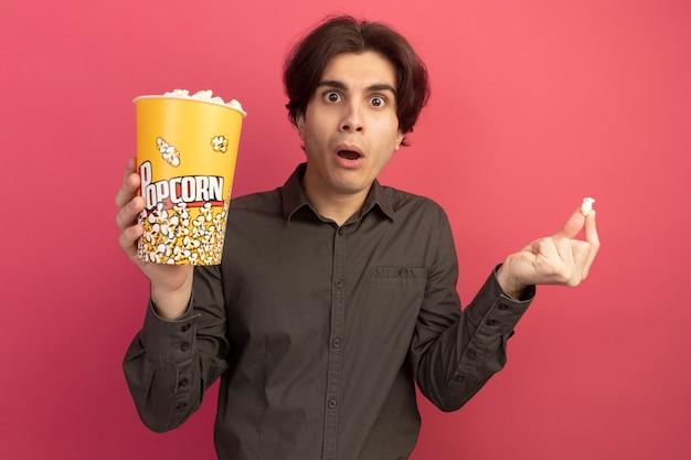 Überraschtes junges gutaussehendes kerl, das schwarzes t-shirt hält, das eimer popcorn mit popcornfrieden lokalisiert auf rosa wand hält