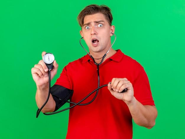 Überraschtes junges hübsches blondes krankes manntragenes stethoskop, das druck zu sich selbst misst und blutdruckmessgerät zeigt, das vorne lokalisiert auf grüner wand betrachtet