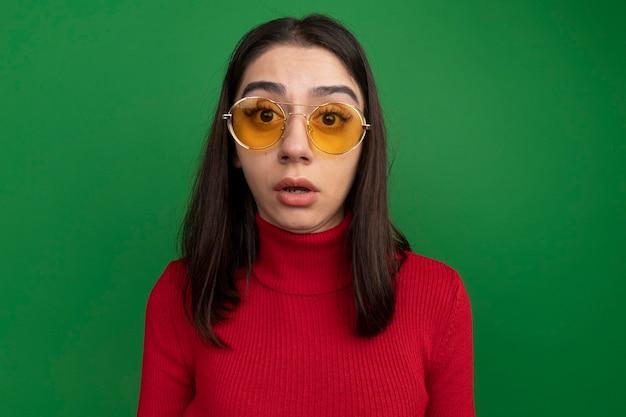 Überraschtes junges hübsches kaukasisches mädchen mit sonnenbrille