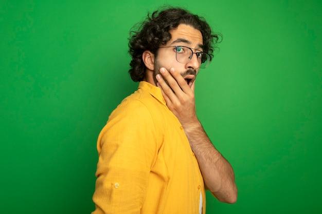 Überraschtes junges hübsches kaukasisches mann, das die brille trägt, die in der profilansicht steht, die kamera betrachtet, die hand auf kinn lokalisiert auf grünem hintergrund mit kopienraum setzt