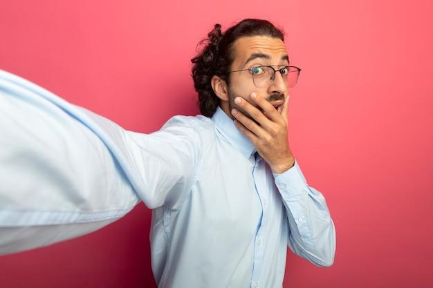 Überraschtes junges hübsches kaukasisches manntragen der brille, die kamera betrachtet, streckt hand in richtung kamera aus, die hand auf mund lokalisiert auf purpurrotem hintergrund mit kopienraum hält