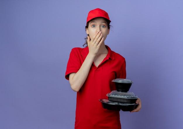 Überraschtes junges hübsches liefermädchen, das rote uniform und kappe hält, die lebensmittelbehälter hält, die hand auf mund lokalisiert auf lila hintergrund mit kopienraum setzen