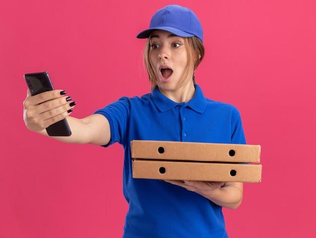 Überraschtes junges hübsches liefermädchen in uniform hält pizzaschachteln und schaut auf telefon auf rosa