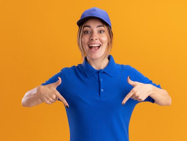 Überraschtes junges hübsches liefermädchen in uniform zeigt mit zwei händen auf orange nach unten