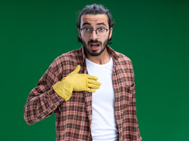 Überraschtes junges hübsches reinigungspersonal, das t-shirt und handschuhe trägt, die hand lokalisiert auf grüne wand setzen