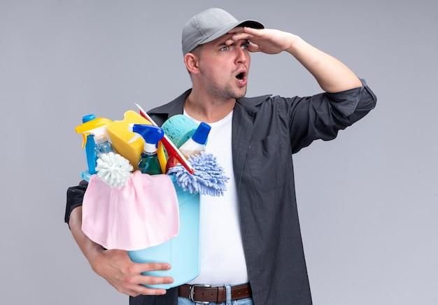 Überraschtes junges hübsches reinigungspersonal, das t-shirt und kappe hält, die eimer mit reinigungswerkzeugen hält, die entfernung mit hand lokalisiert auf weißer wand betrachten