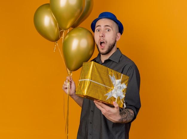 Überraschtes junges hübsches slawisches partei-kerl, das parteihut trägt, der in der profilansicht hält ballons und geschenkpackung betrachtet kamera betrachtet auf orange hintergrund mit kopienraum