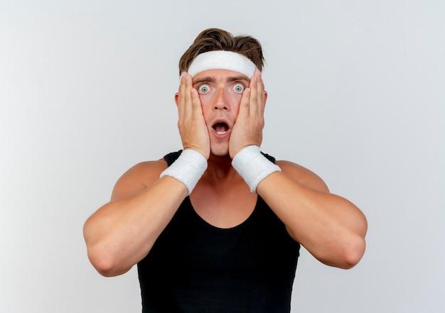Überraschtes junges hübsches sportliches mann-tragen des stirnbandes und der armbänder, die hände auf gesicht lokalisiert auf weißer wand setzen