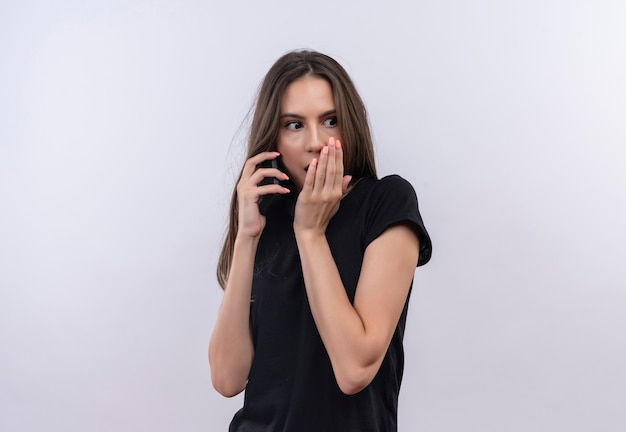 Überraschtes junges kaukasisches mädchen, das schwarzes t-shirt trägt, spricht am telefon bedeckten mund auf lokalisiertem weißem hintergrund