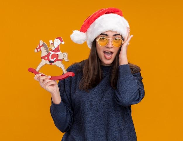 Überraschtes junges kaukasisches mädchen in sonnenbrille mit weihnachtsmütze legt die hand auf das gesicht und hält den weihnachtsmann auf der schaukelpferddekoration, die auf orangefarbener wand mit kopienraum isoliert ist