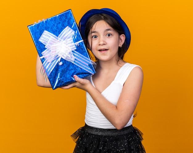 Überraschtes junges kaukasisches mädchen mit blauem partyhut, das geschenkbox isoliert auf oranger wand mit kopienraum hält
