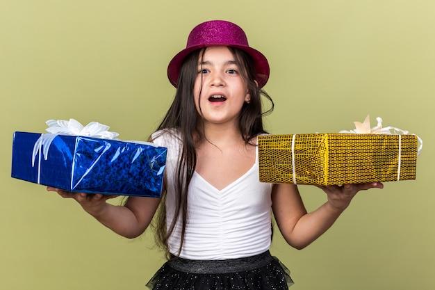 Überraschtes junges kaukasisches mädchen mit lila partyhut, das eine geschenkbox an jeder hand hält, isoliert auf olivgrüner wand mit kopierraum