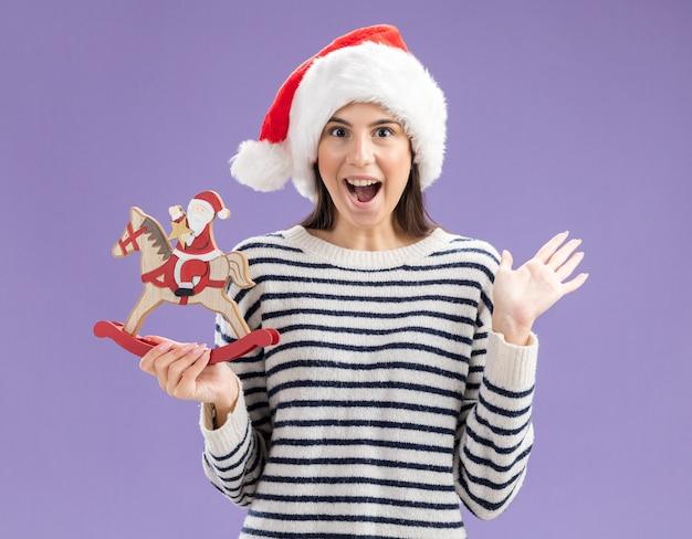Überraschtes junges kaukasisches mädchen mit weihnachtsmütze hält den weihnachtsmann auf schaukelpferddekoration und hält die hand isoliert auf lila wand mit kopierraum