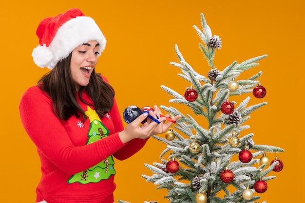 Überraschtes junges kaukasisches mädchen mit weihnachtsmütze hält und betrachtet glaskugelverzierungen, die neben weihnachtsbaum lokalisiert auf orange hintergrund mit kopienraum stehen