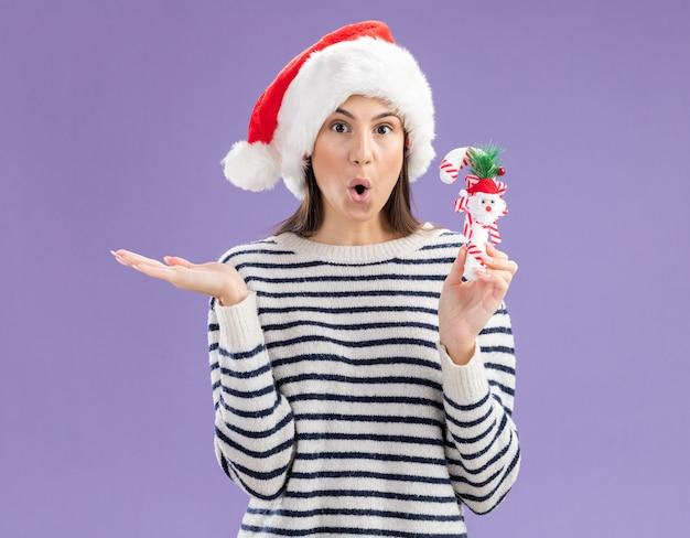 Überraschtes junges kaukasisches mädchen mit weihnachtsmütze hält zuckerstange und hält hand offen