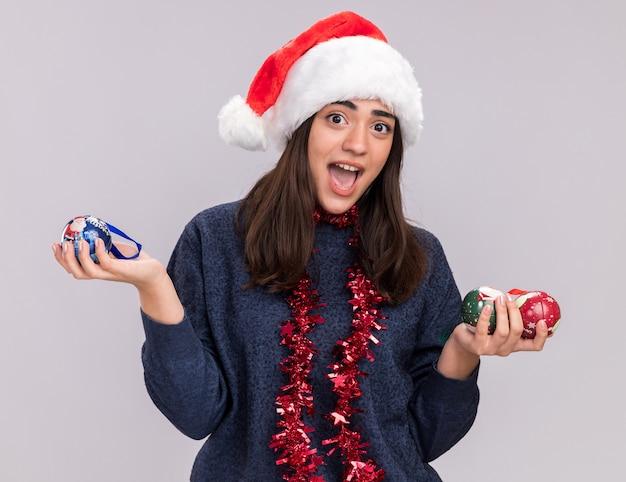 Überraschtes junges kaukasisches mädchen mit weihnachtsmütze und girlande um hals hält glaskugelverzierungen