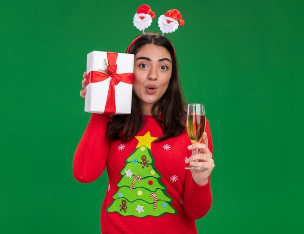 Überraschtes junges kaukasisches mädchen mit weihnachtsstirnband hält ein glas champagner und eine weihnachtsgeschenkbox isoliert auf grüner wand mit kopierraum