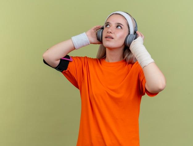 Überraschtes junges kaukasisches sportliches mädchen mit hosenträgern auf kopfhörern, das stirnband-armbänder und telefonarmband trägt, schaut nach oben