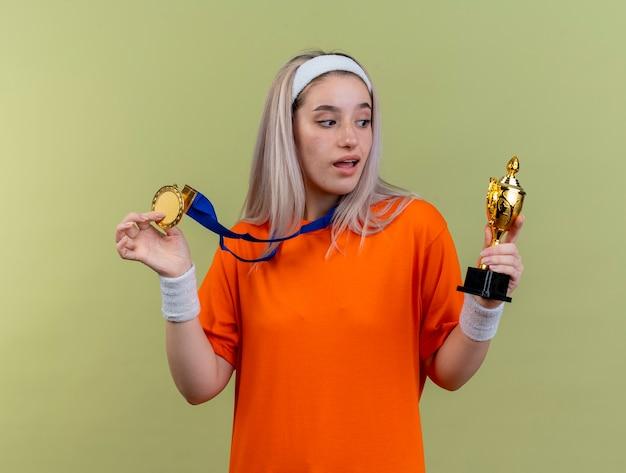 Überraschtes junges kaukasisches sportliches mädchen mit hosenträgern, das stirnband und armbänder trägt, hält goldmedaille und schaut auf den siegerpokal