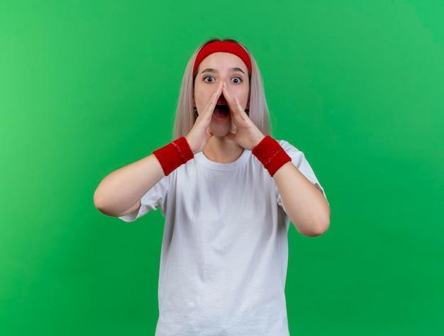 Überraschtes junges kaukasisches sportliches mädchen mit zahnspangen, die stirnband tragen