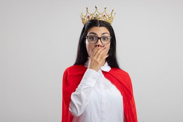Überraschtes junges kaukasisches superheldenmädchen, das brille und krone betrachtet kamera betrachtet, die hand auf mund lokalisiert auf weißem hintergrund mit kopienraum hält