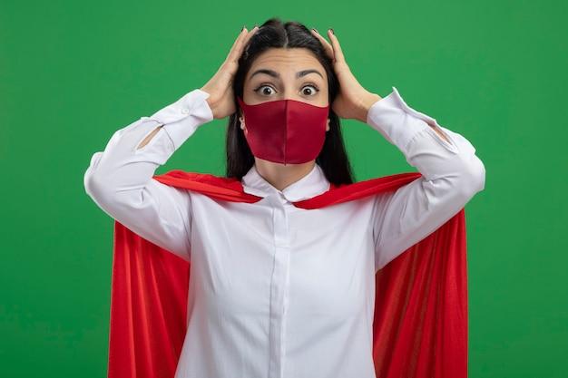 Überraschtes junges kaukasisches superheldenmädchen, das maske trägt, die hände auf ihren kopf setzt und kamera lokalisiert auf grünem hintergrund betrachtet