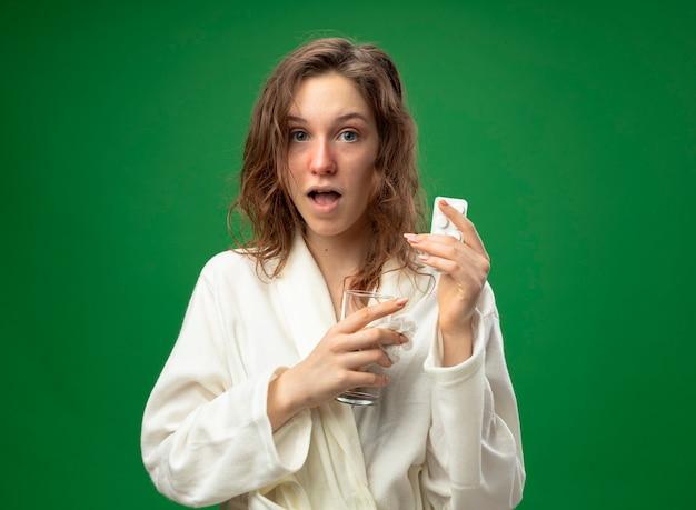 Überraschtes junges krankes mädchen, das weißes gewand hält, das glas wasser mit den auf grün lokalisierten pillen hält