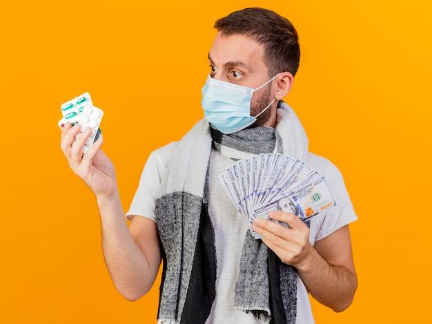 Überraschtes junges krankes manntragen wintermütze, das bargeld hält und pillen in seiner hand lokalisiert auf gelbem hintergrund betrachtet
