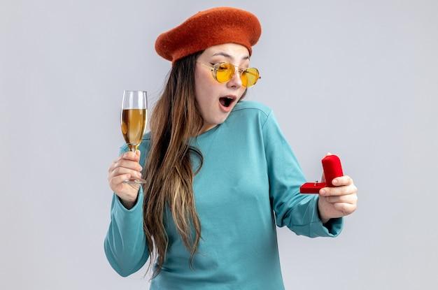 Überraschtes junges mädchen am valentinstag mit hut mit brille, das ein glas champagner mit ehering auf weißem hintergrund hält holding